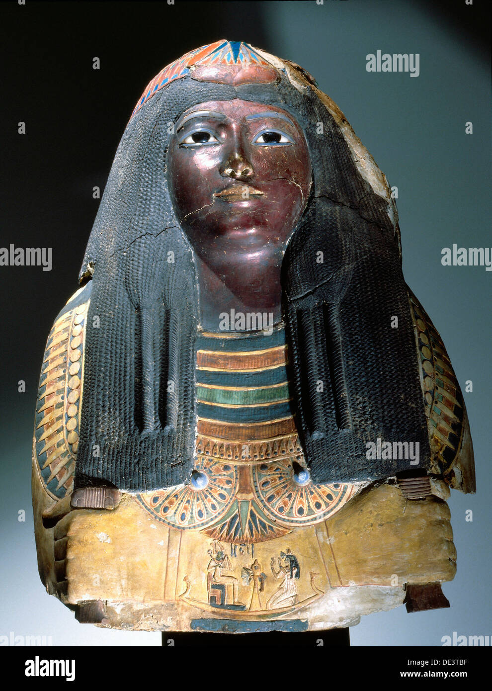 Upper part of an anthropomorphic coffin with blackened face, lotus ornamented wig, chest ornaments and a picture of the deceased - Stock Image