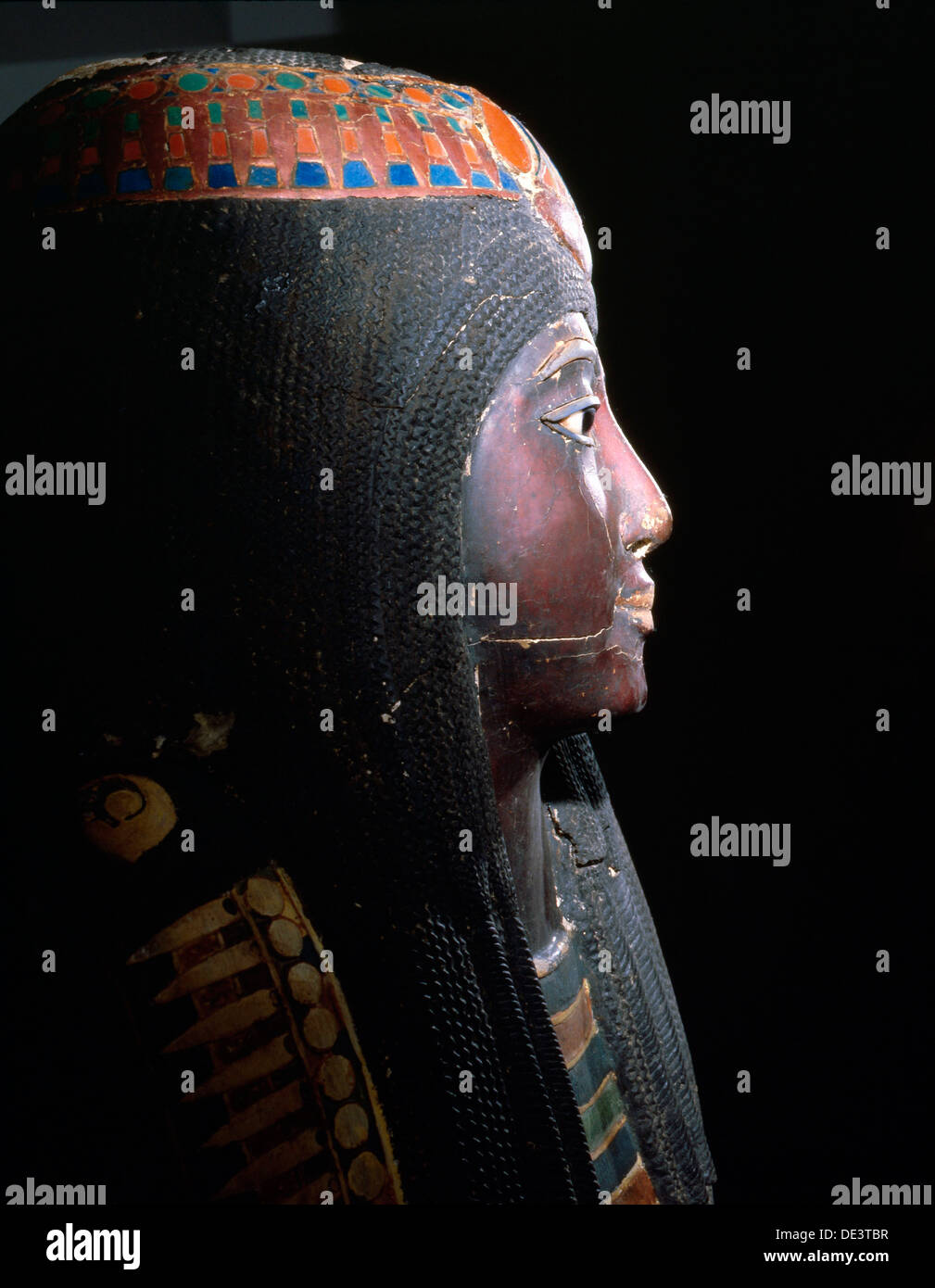 Upper part of an anthropomorphic coffin with blackened face, lotus ornamented wig, chest ornaments, and a picture of the decease - Stock Image