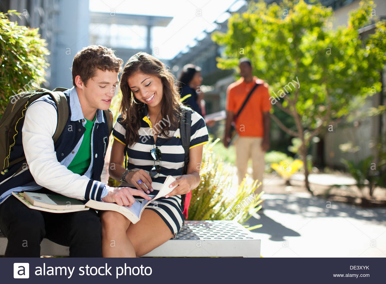 Students reading book together outdoors - Stock Image