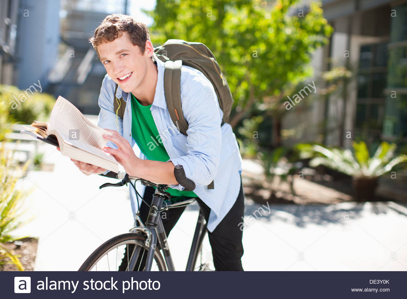 Student reading on bicycle - Stock Image