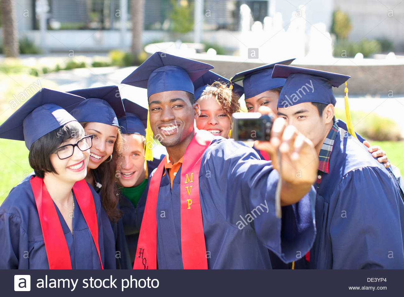 Graduates taking picture of themselves - Stock Image