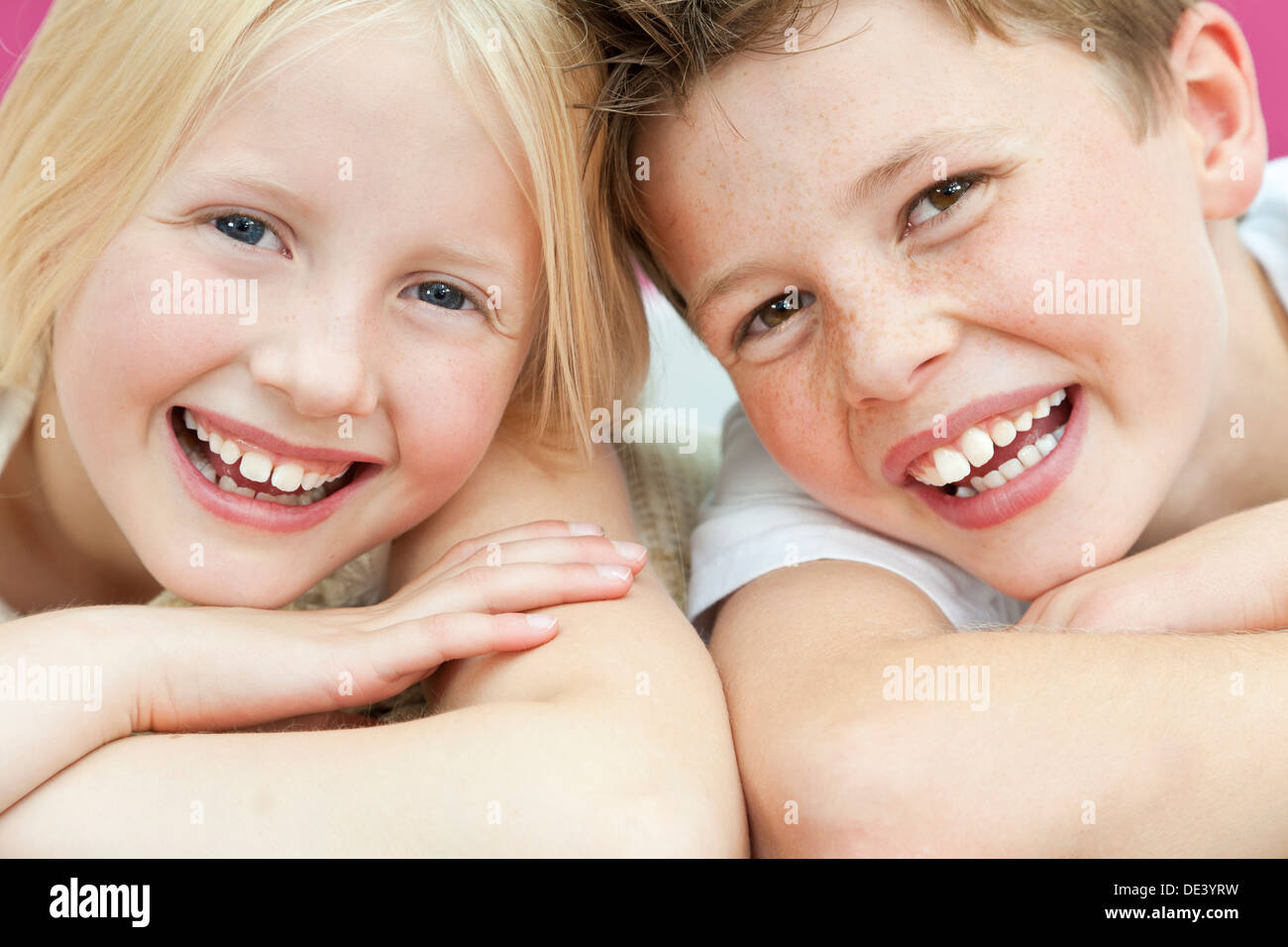 Happy boy and girl, sister and brother laughing with big toothy smiles - Stock Image