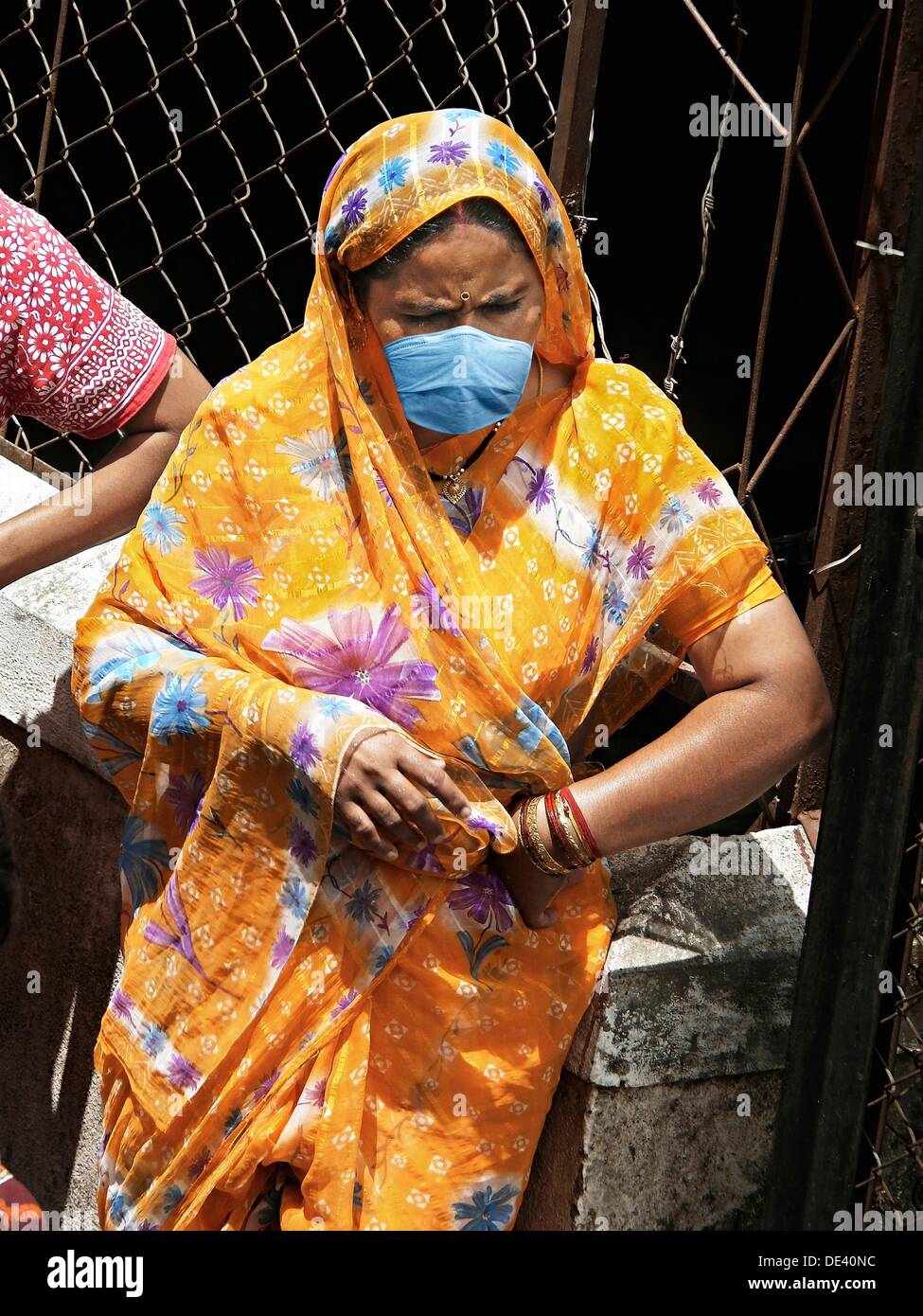 A woman at community water tap with mask, India - Stock Image