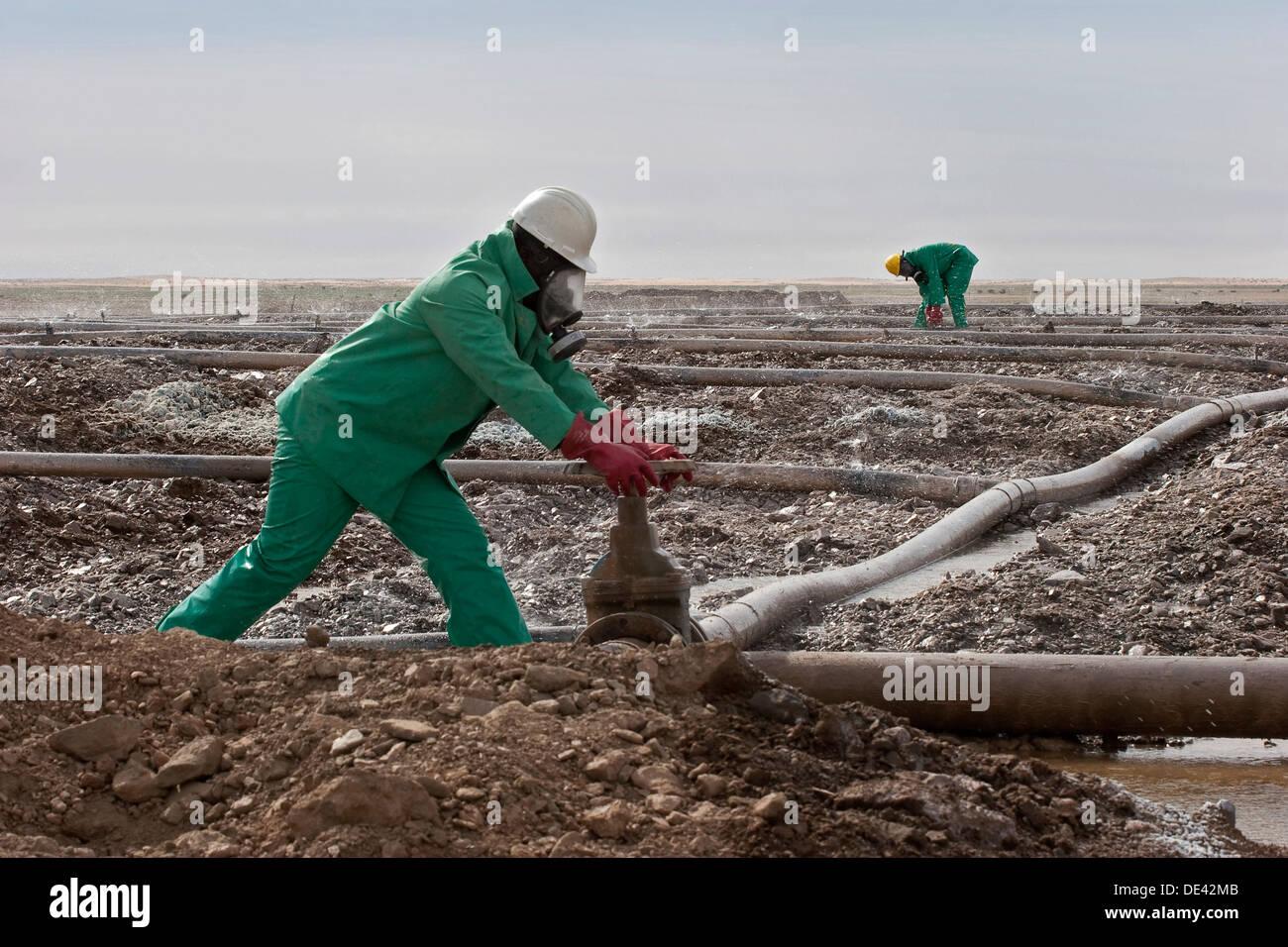 Operator adjusting valve on sprinkler system on dump heap leach pad. Surface gold mine. Mauritania, North West Africa - Stock Image