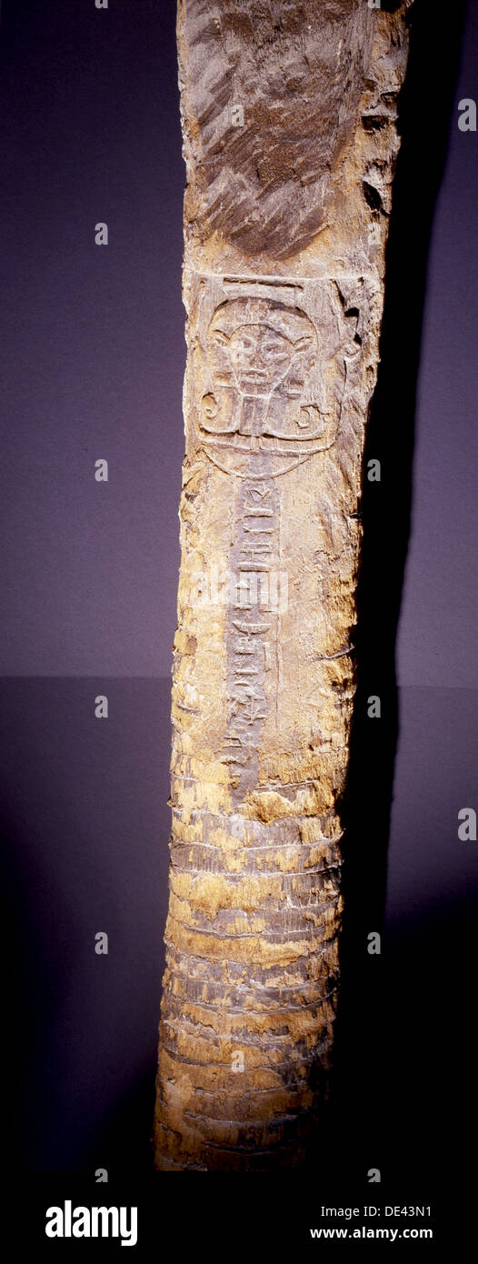 Trunk of a plam tree inscribe with hieroglyphs and a Hathor head carved above the inscription. - Stock Image