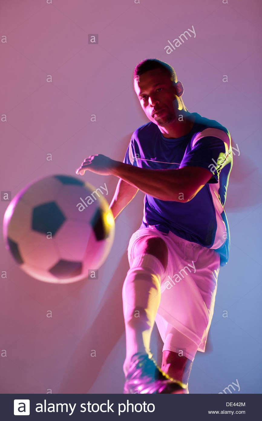 Soccer player kicking ball - Stock Image