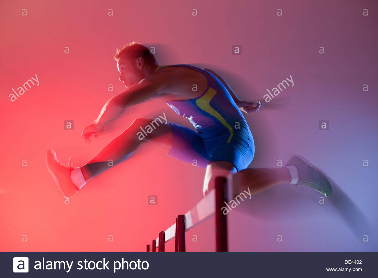Blurred view of athlete jumping hurdles - Stock Image