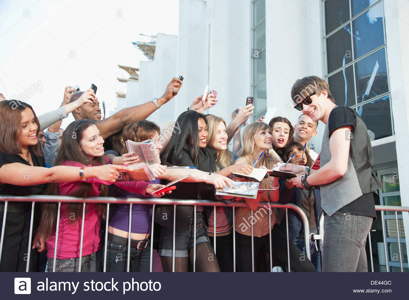 Celebrity signing autographs for fans - Stock Image
