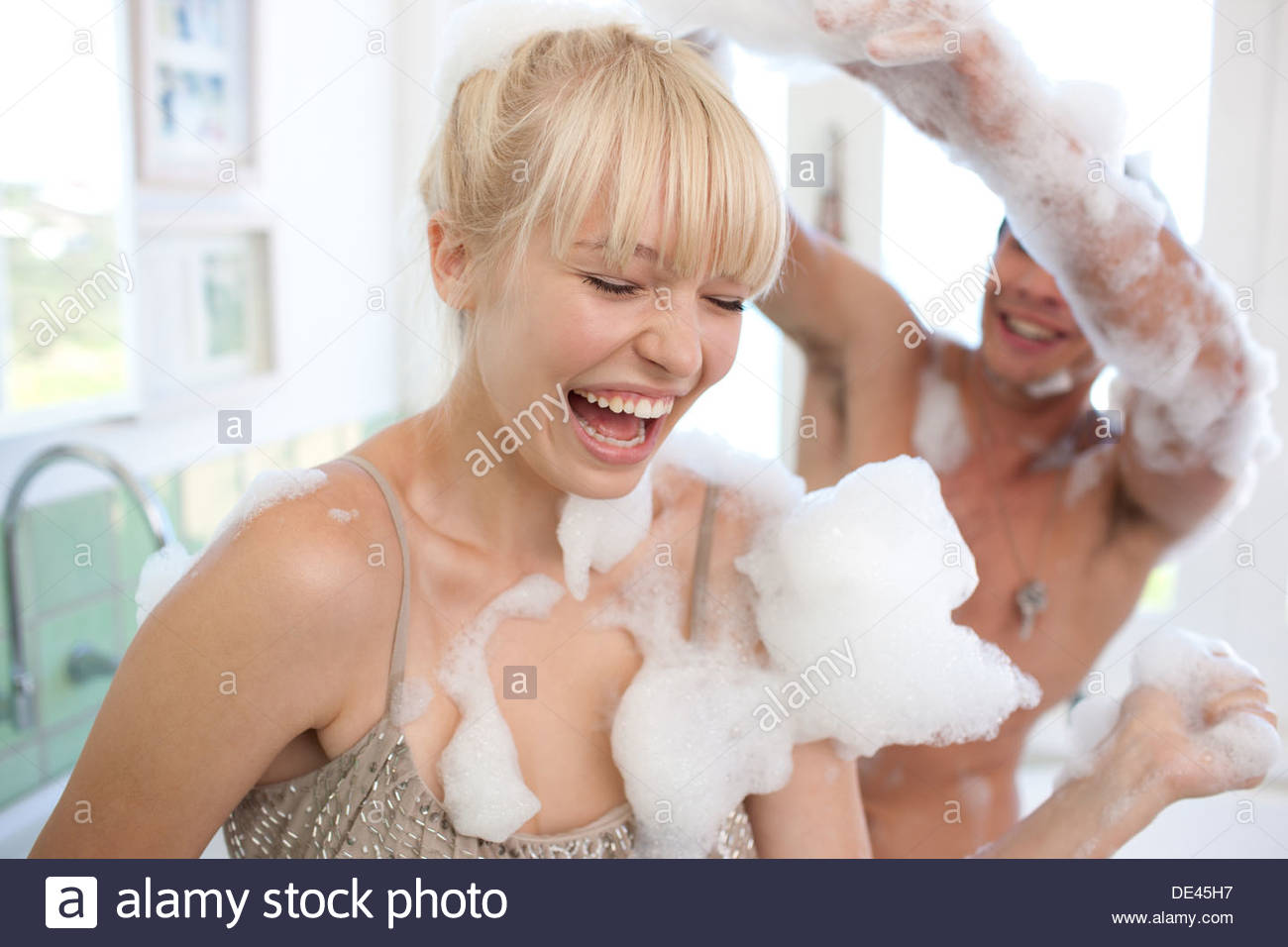 Couple covered with soap suds in bathroom - Stock Image