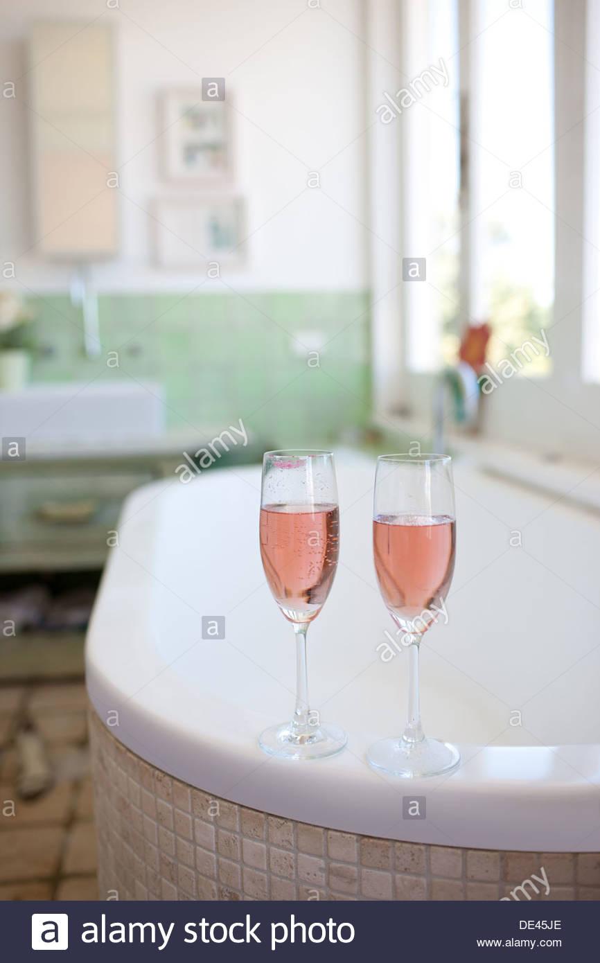 Champagne on edge of bathtub - Stock Image