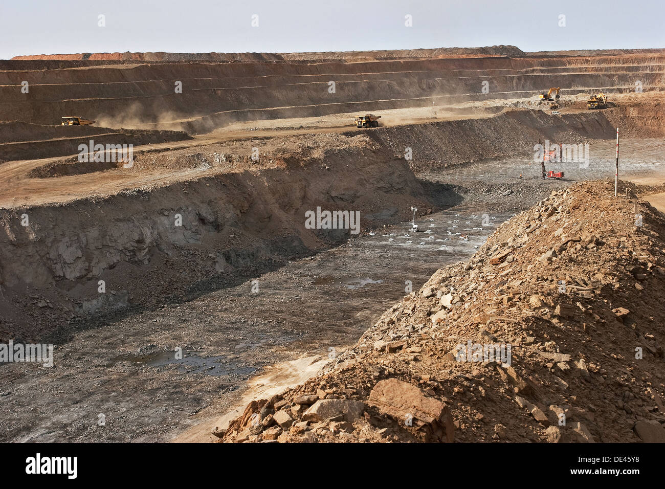 Surface pit gold mining, drilling holes for charges before blast with excavators and haul trucks on bench behind, Mauritania - Stock Image