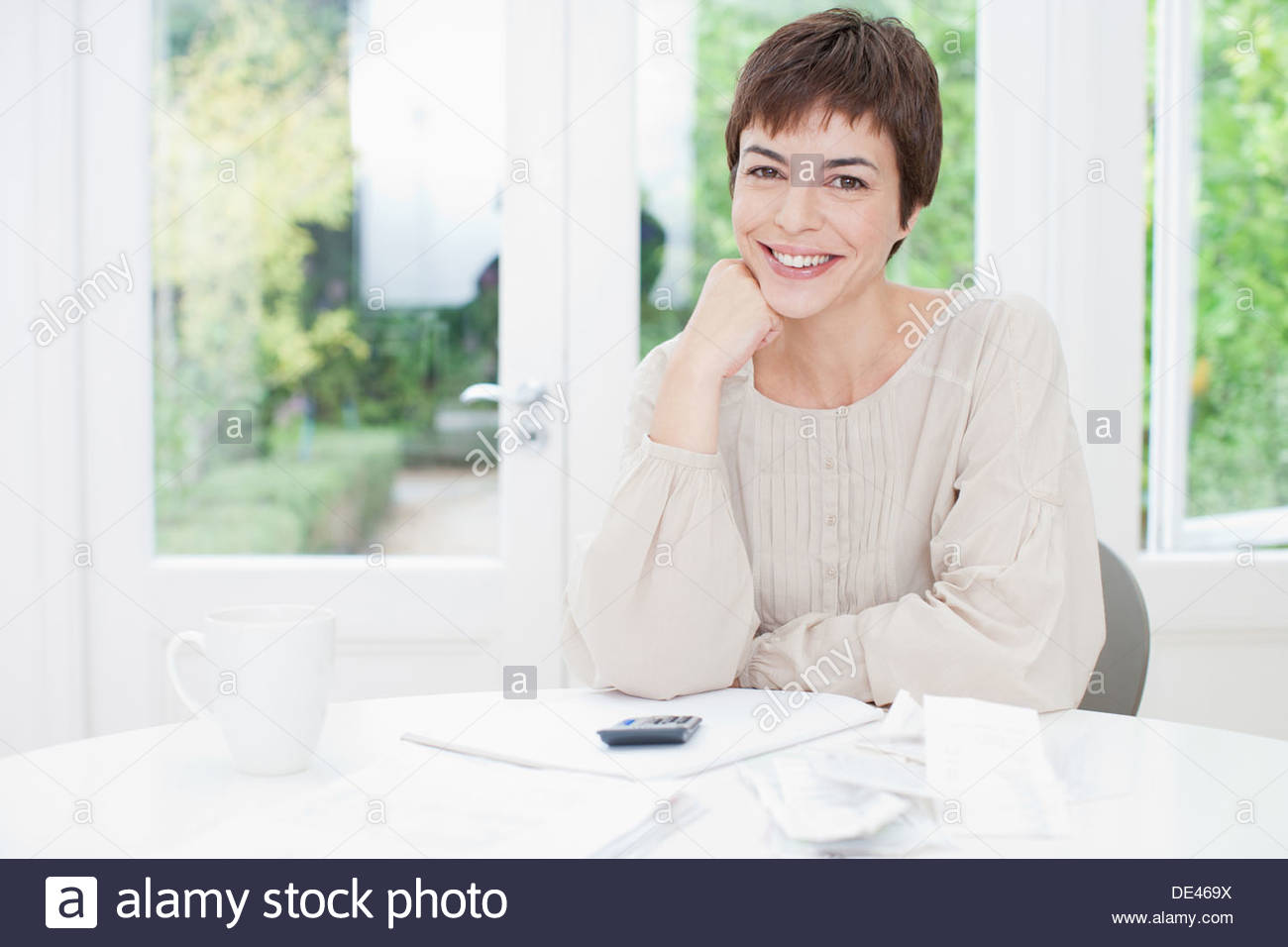 Smiling woman sitting at table paying bills - Stock Image