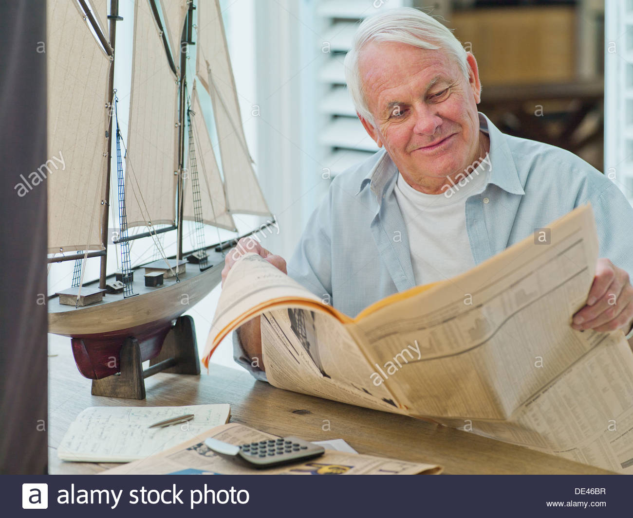 Man reading newspaper near model sailboat - Stock Image