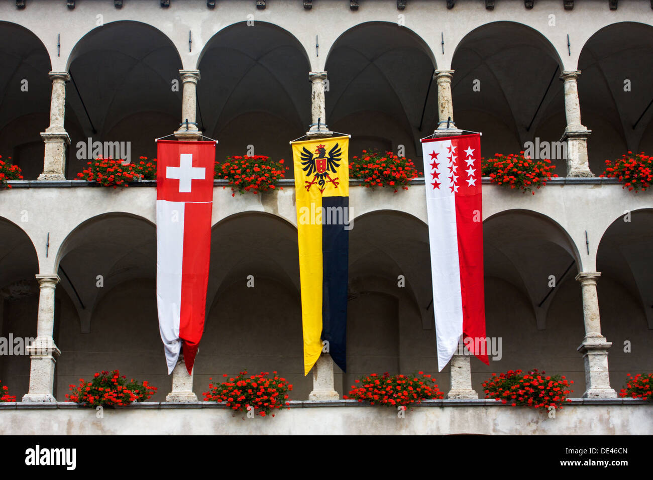 Three banners (one of Switzerland, one of Wallis and one of Brig) hanging from the balcony of a swiss palace - Stock Image