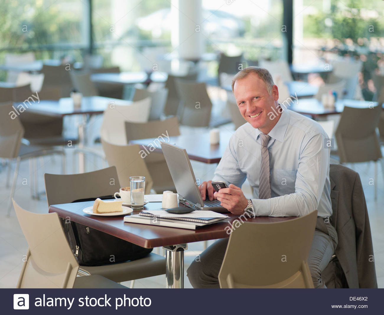 Businessman looking at cell phone in cafeteria - Stock Image