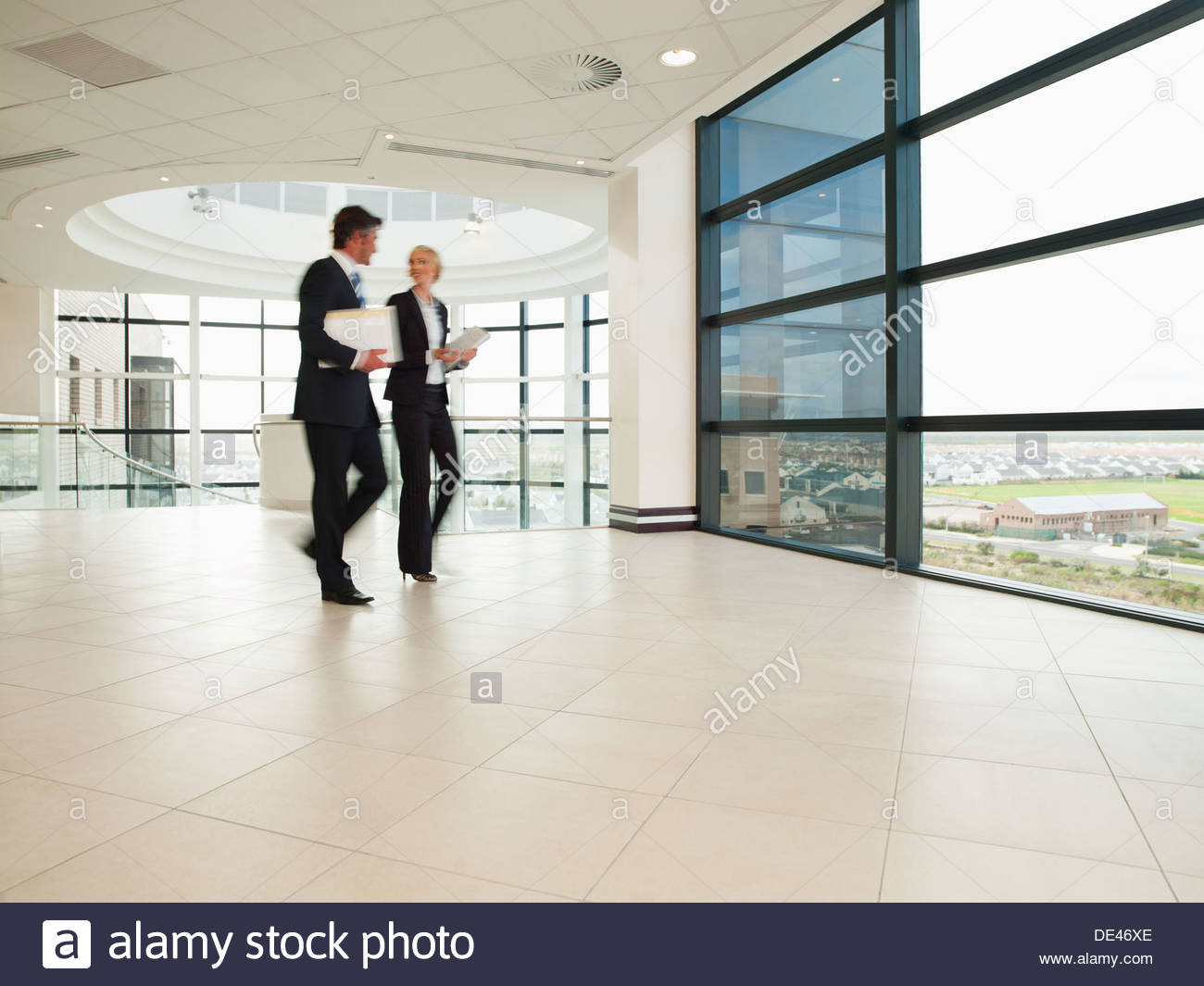 Business people walking through office lobby - Stock Image