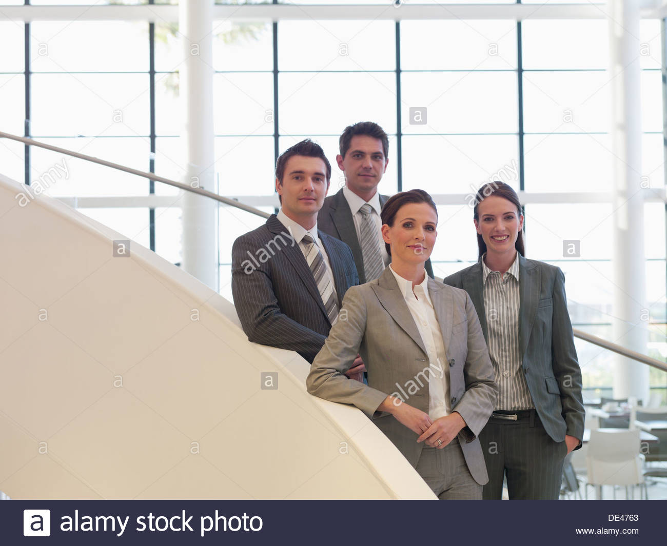 Business people standing on staircase - Stock Image