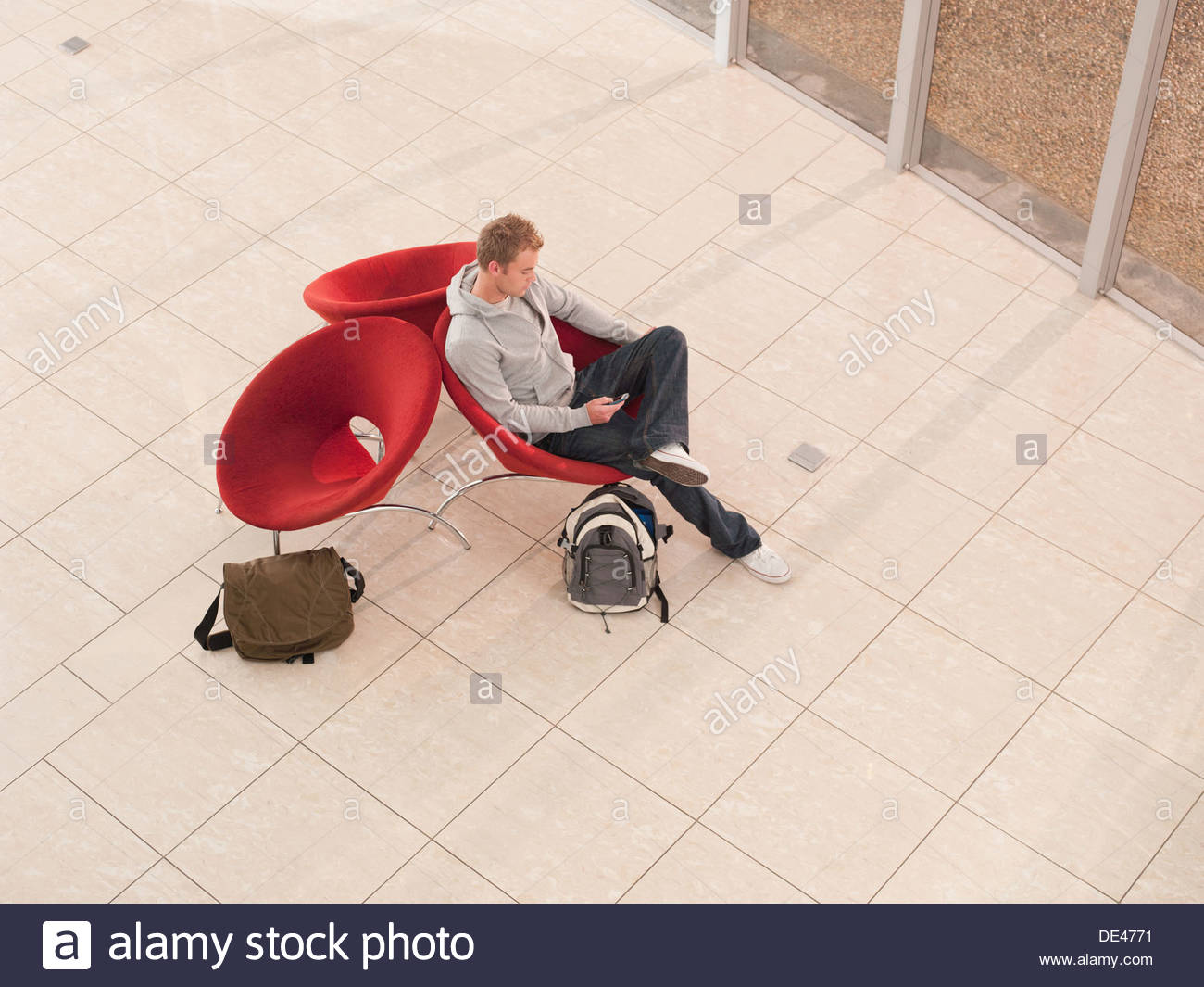 College student sitting in lobby chair with cell phone - Stock Image