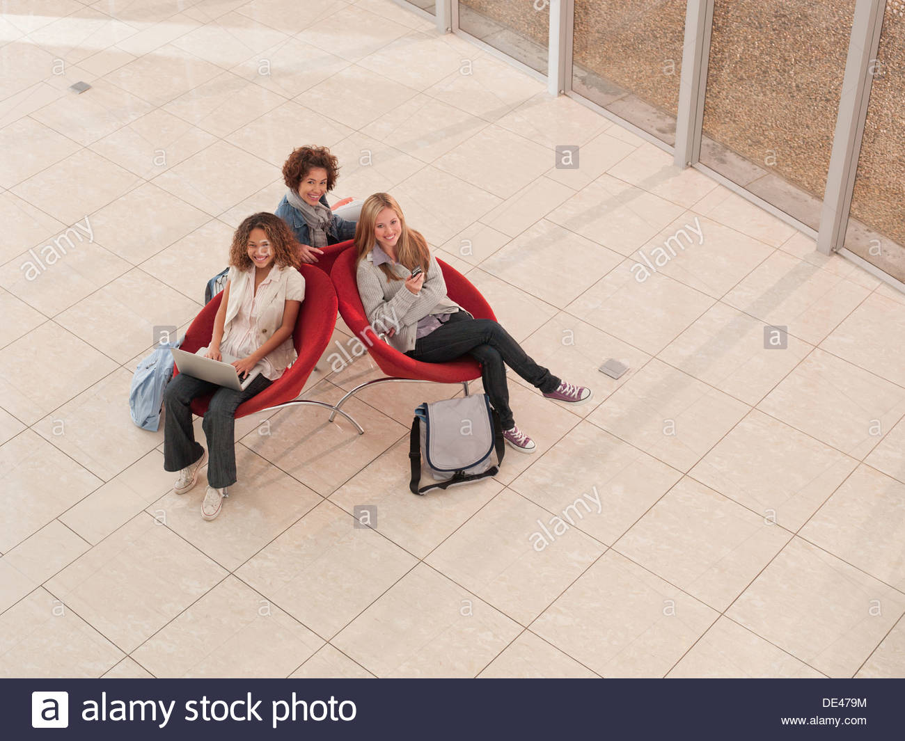 College friends using laptop and cell phone in lobby Stock Photo