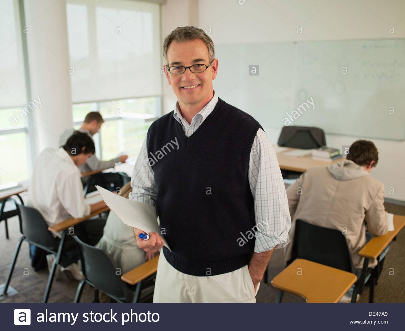 Smiling professor in classroom - Stock Image