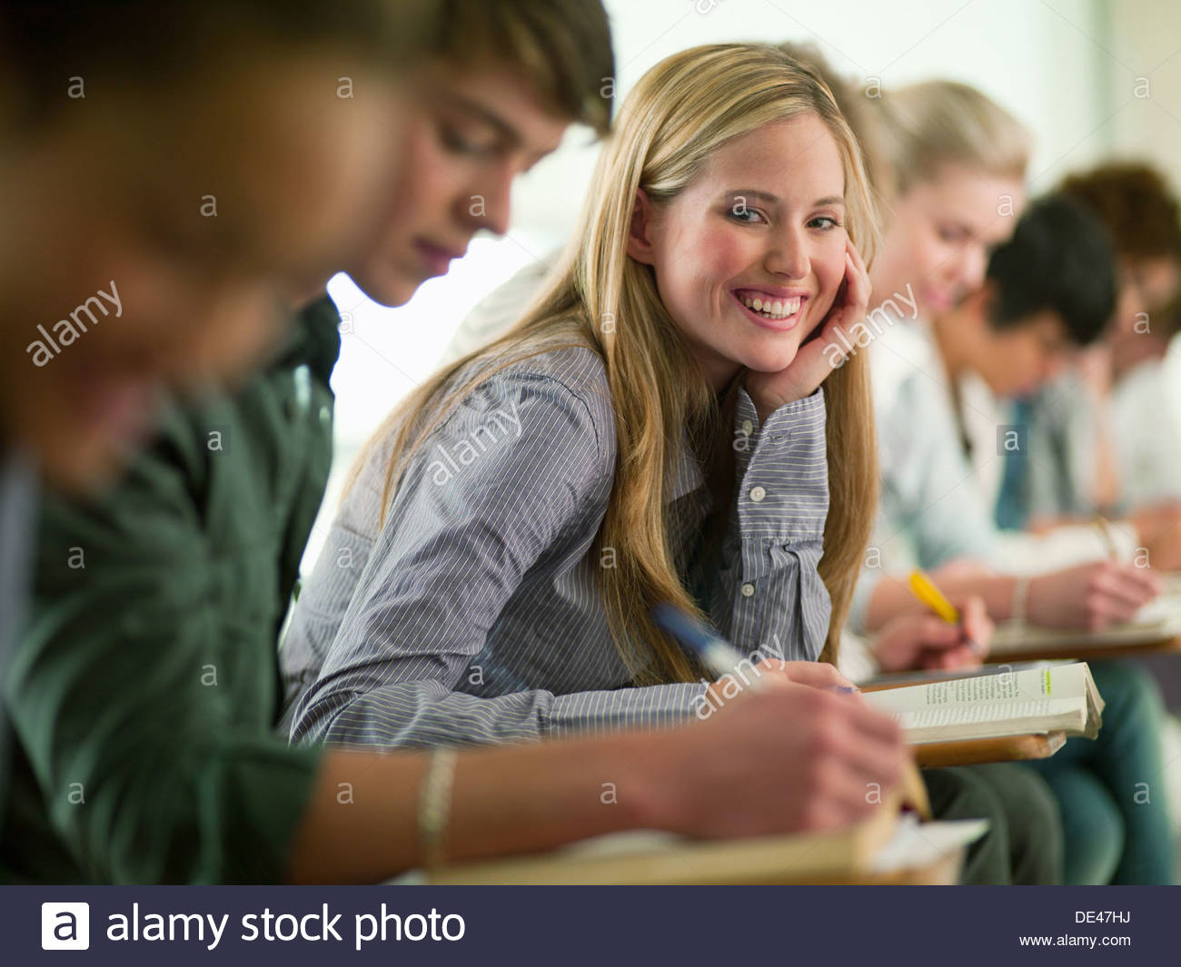 Smiling college student sitting at desk in classroom - Stock Image