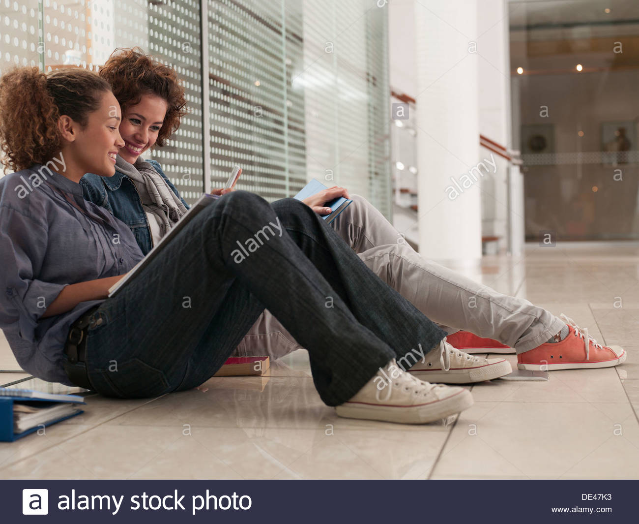 College students with notebooks sitting on floor and laughing - Stock Image