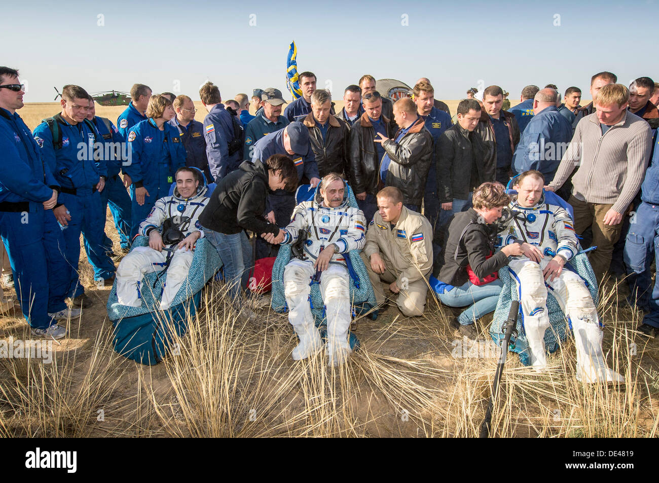 Expedition 36 Flight Engineer Chris Cassidy of NASA, left, Commander Pavel Vinogradov of the Russian Federal Space Agency, center, and, Flight Engineer Alexander Misurkin of Roscosmos, sit in chairs outside the Soyuz TMA-08M capsule just minutes after landing September 11, 2013 near the town of Zhezkazgan, Kazakhstan. Vinogradov, Misurkin and Cassidy returned to Earth after five and a half months on the International Space Station. - Stock Image