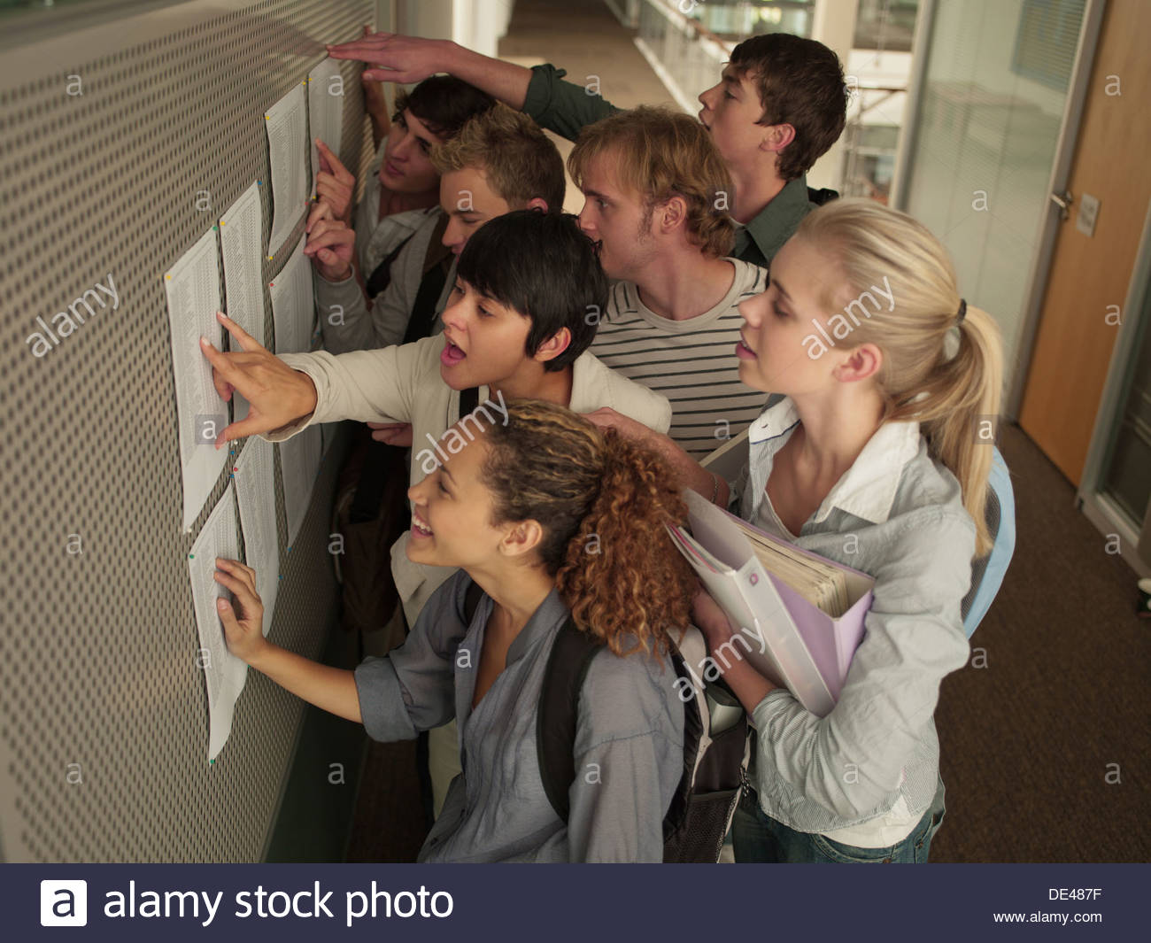 College students checking test scores in corridor - Stock Image