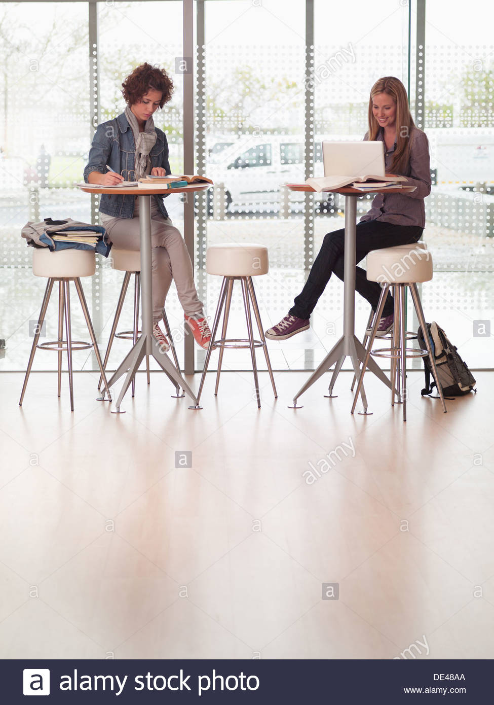 College students sitting at table using laptop and writing - Stock Image