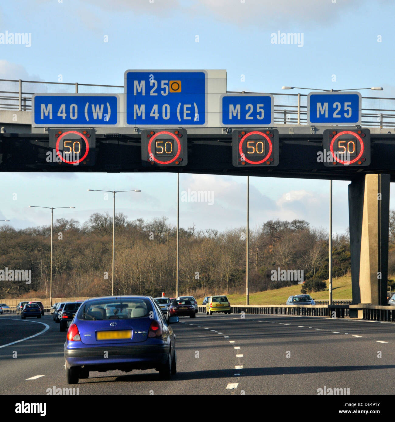 Variable speed limit signs on overhead gantry illuminated on M25 motorway near junction with M40 - Stock Image