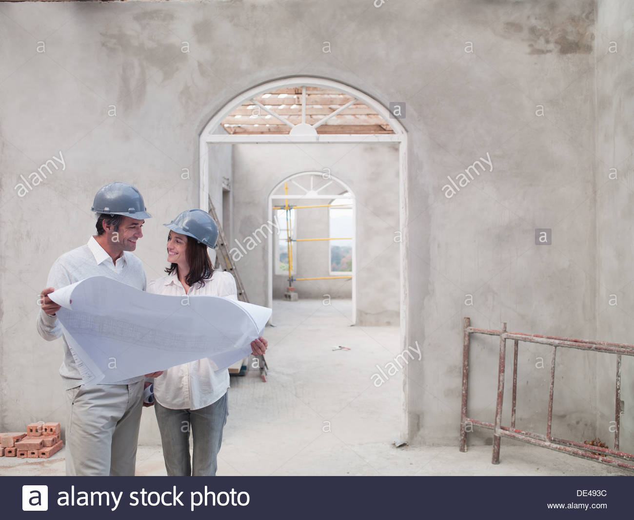 Couple holding blueprints in house under construction Stock Photo