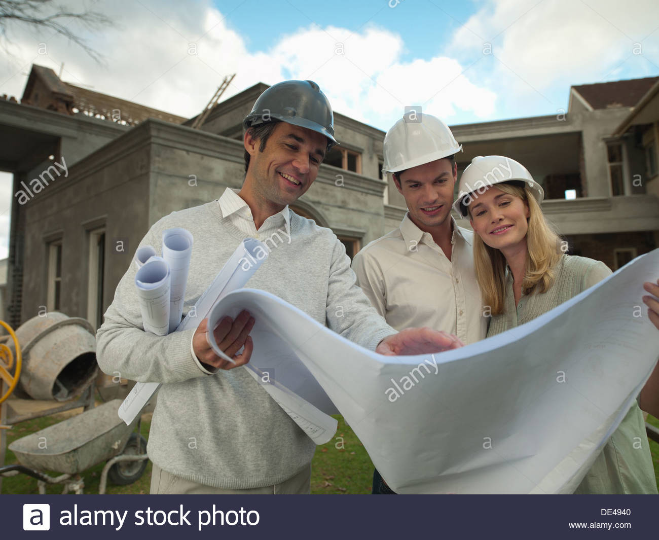 Architect and couple looking at blueprints outside house under construction - Stock Image