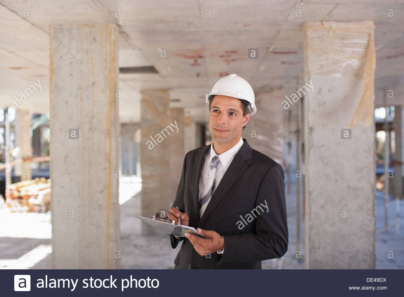 Businessman in hard-hat on construction site - Stock Image