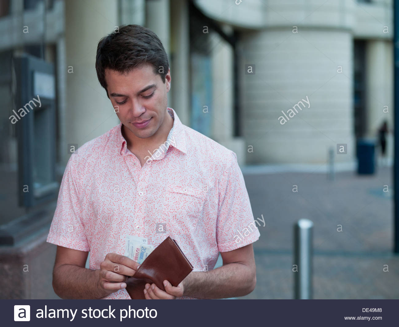 Man holding pocket near ATM machine - Stock Image