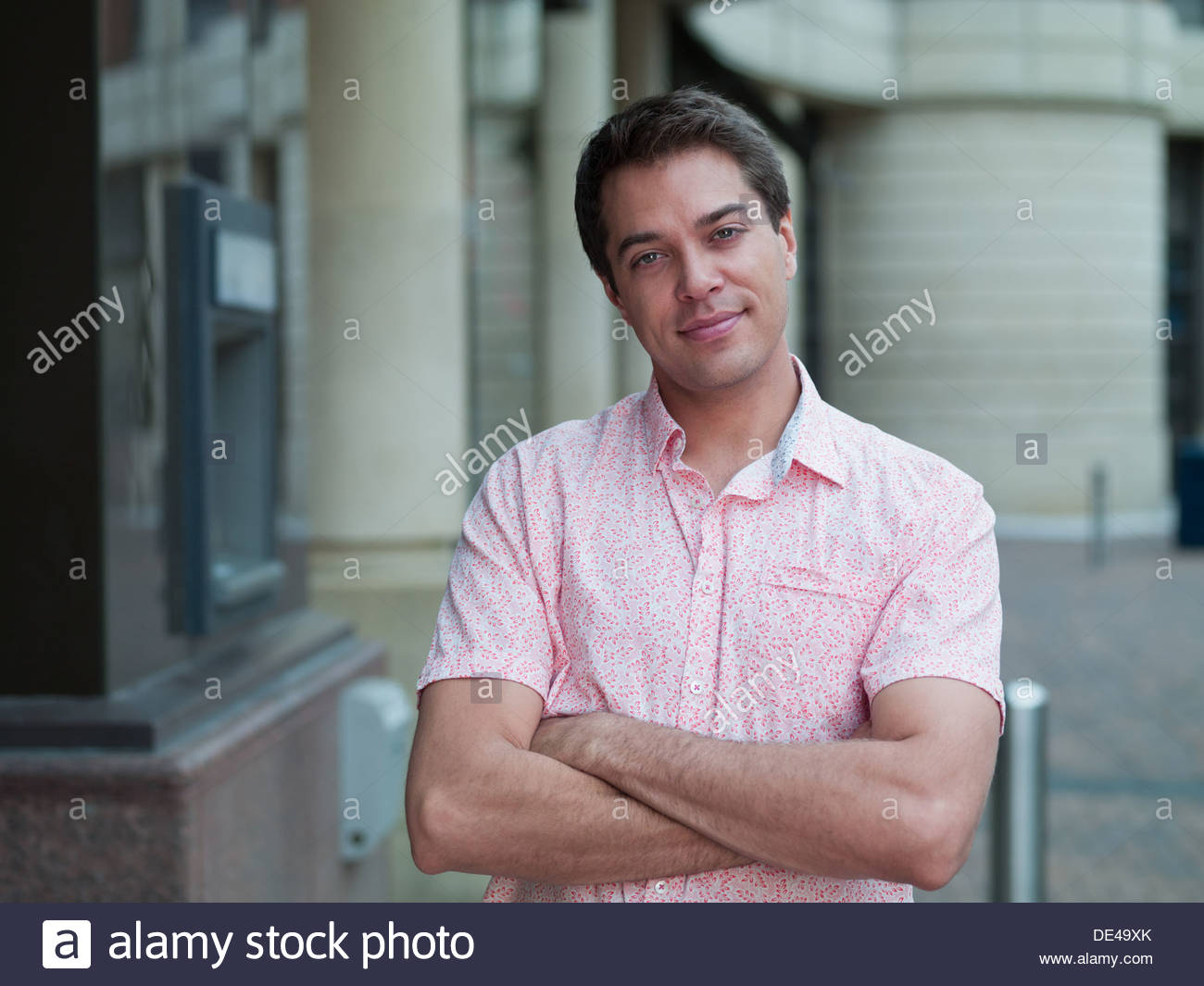 Smiling man with arms crossed near ATM machine - Stock Image