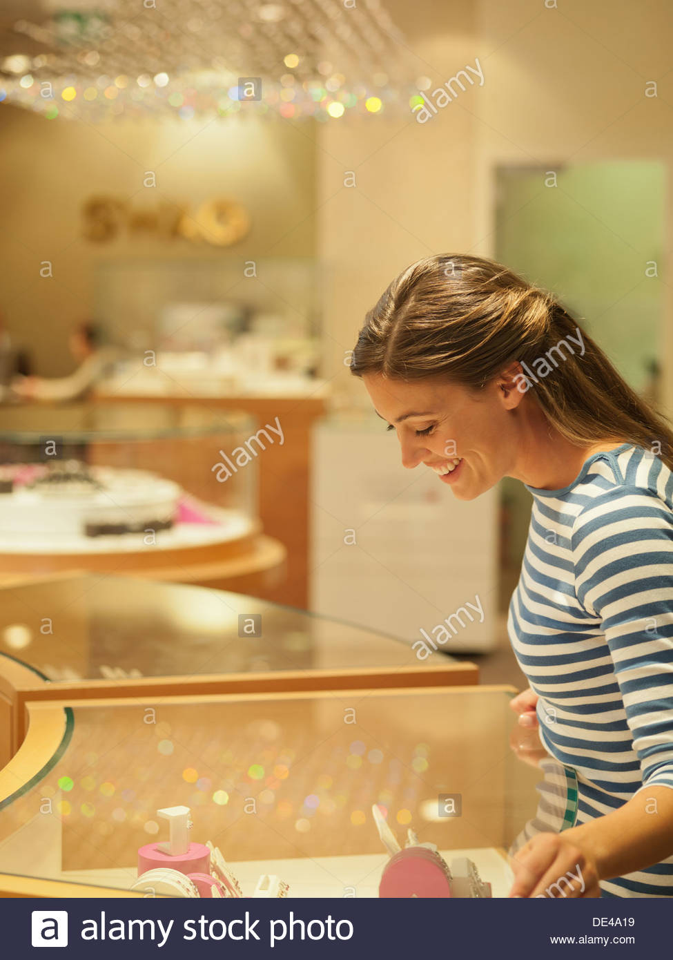 Smiling woman looking at jewelry in display case - Stock Image