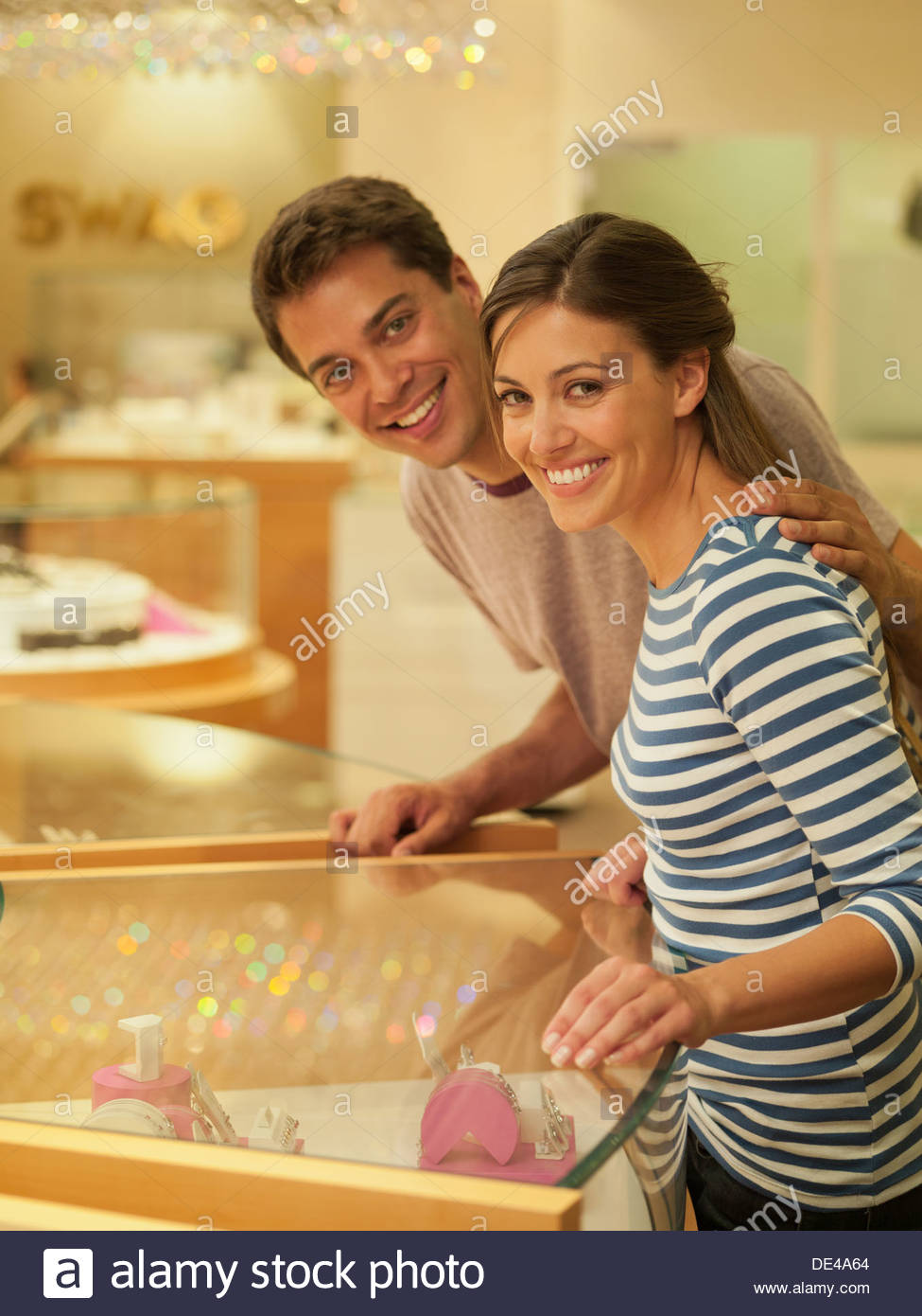 Smiling couple looking at jewelry case - Stock Image