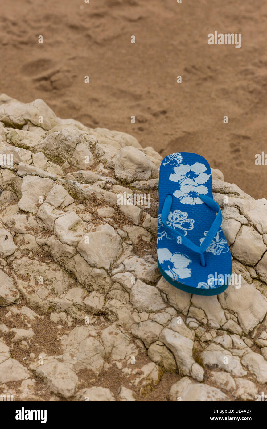 Single Flip Flop on a rock on a beach - Stock Image