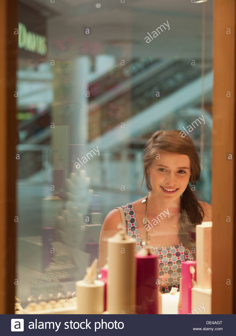 Teenage girl looking at jewelry in display case - Stock Image