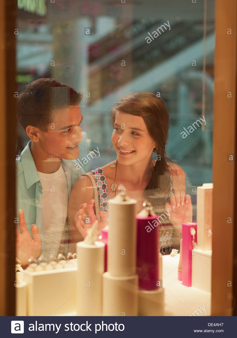 Smiling couple looking at jewelry in display case Stock Photo