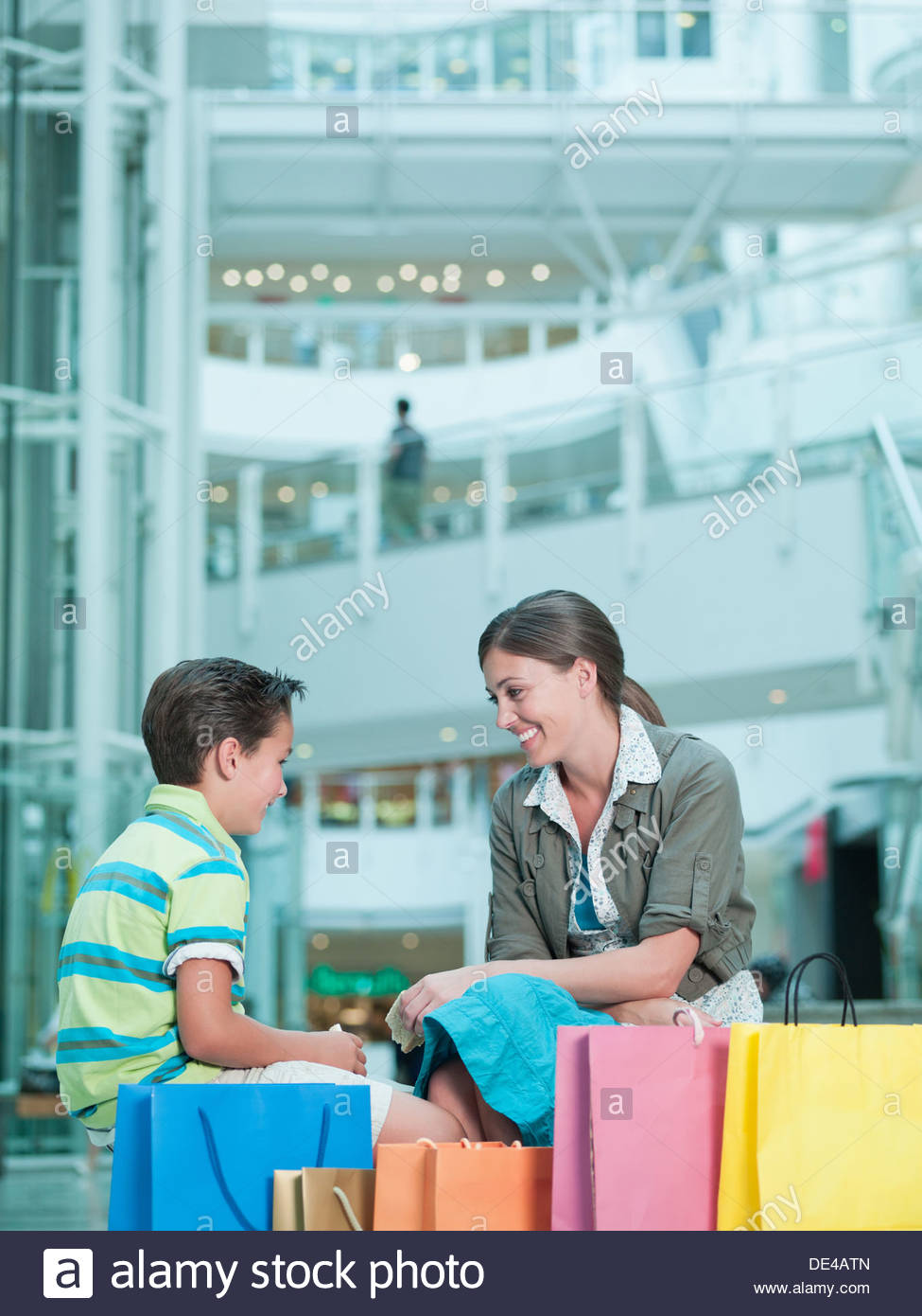 Mother and son with shopping bags in mall - Stock Image