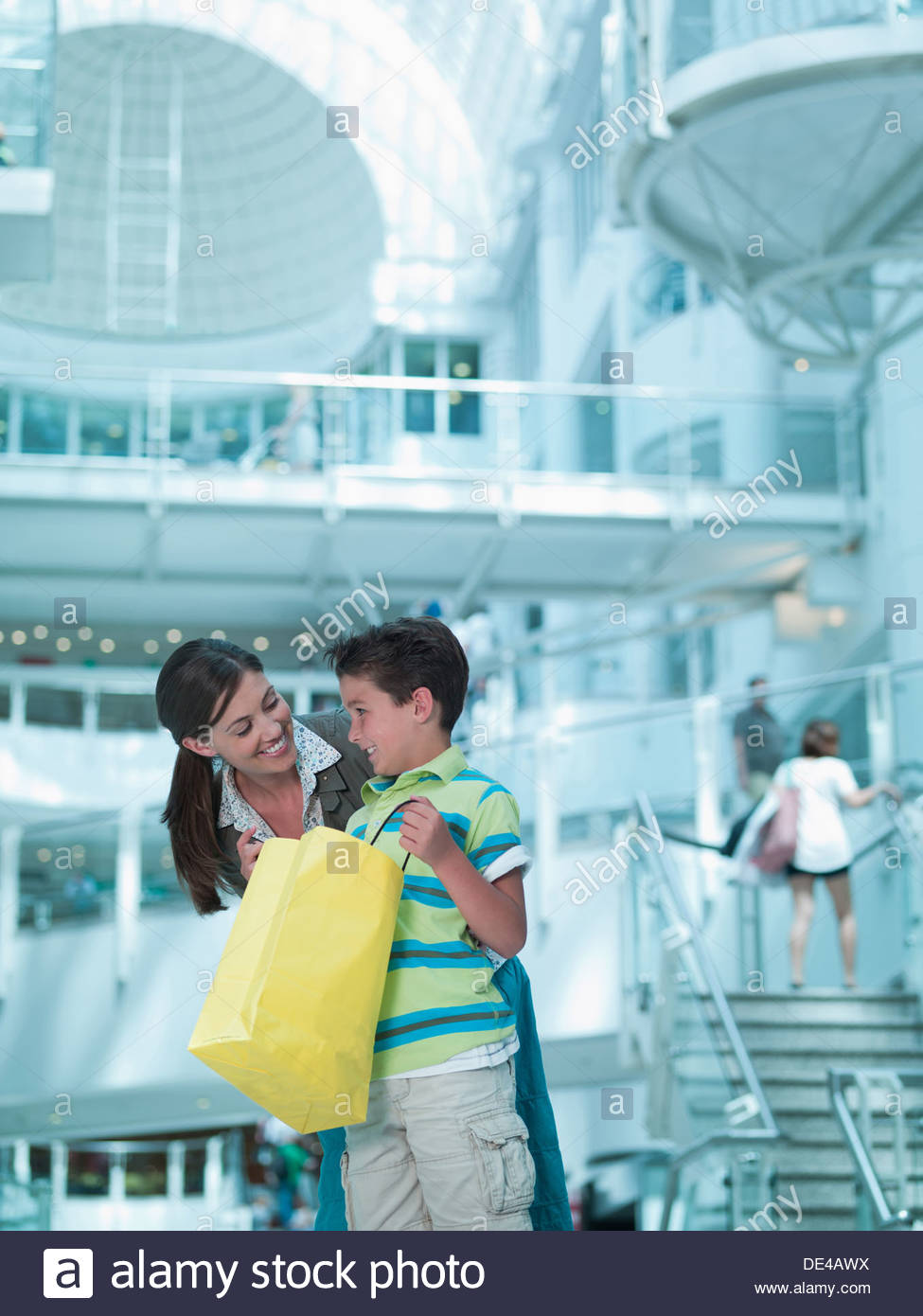 Mother and son looking in shopping bags in mall - Stock Image
