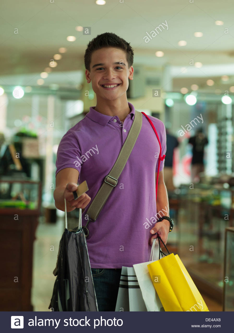 Smiling man display credit card  with carrying shopping bags in store - Stock Image