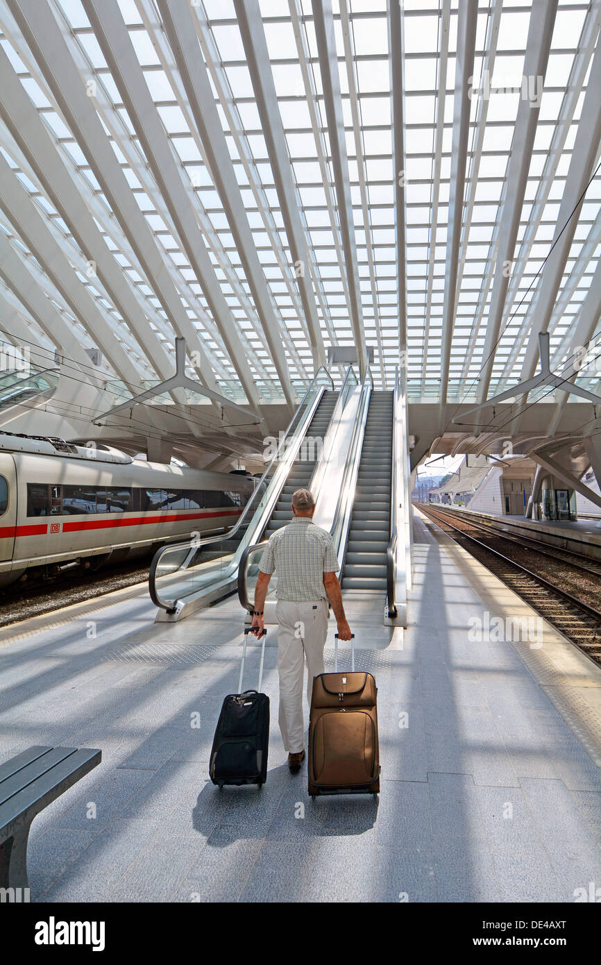 Model release senior man railway passenger person walking with suitcase luggage on train station platform escalator Liège modern building glass roof - Stock Image
