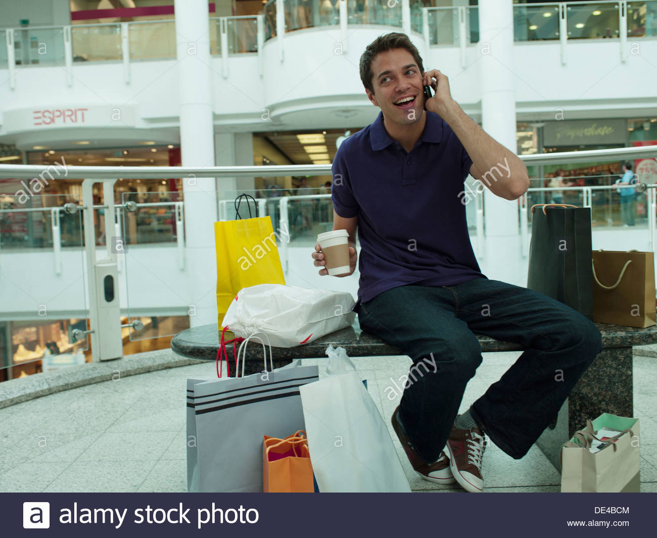 Smiling man in shopping mall talking on cell phone - Stock Image