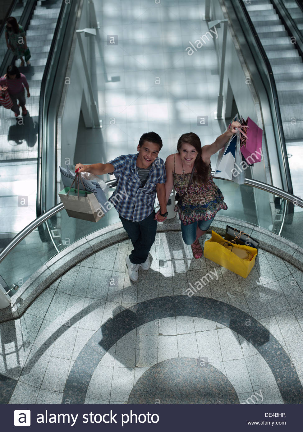 Couple holding shopping bags on balcony in mall - Stock Image