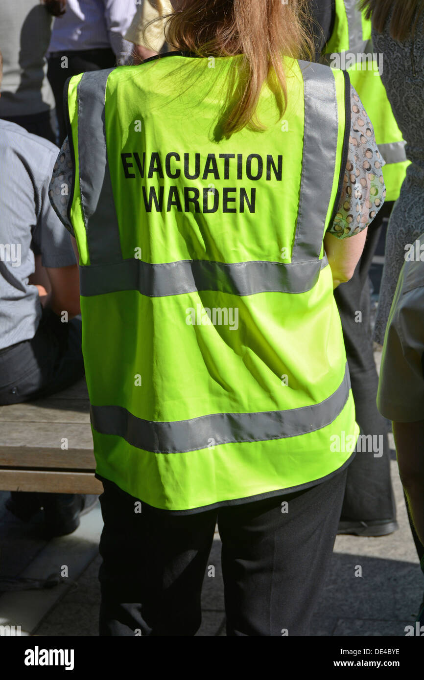 Close up of high visibility vest worn by evacuation warden during practice mass office workforce fire drill - Stock Image