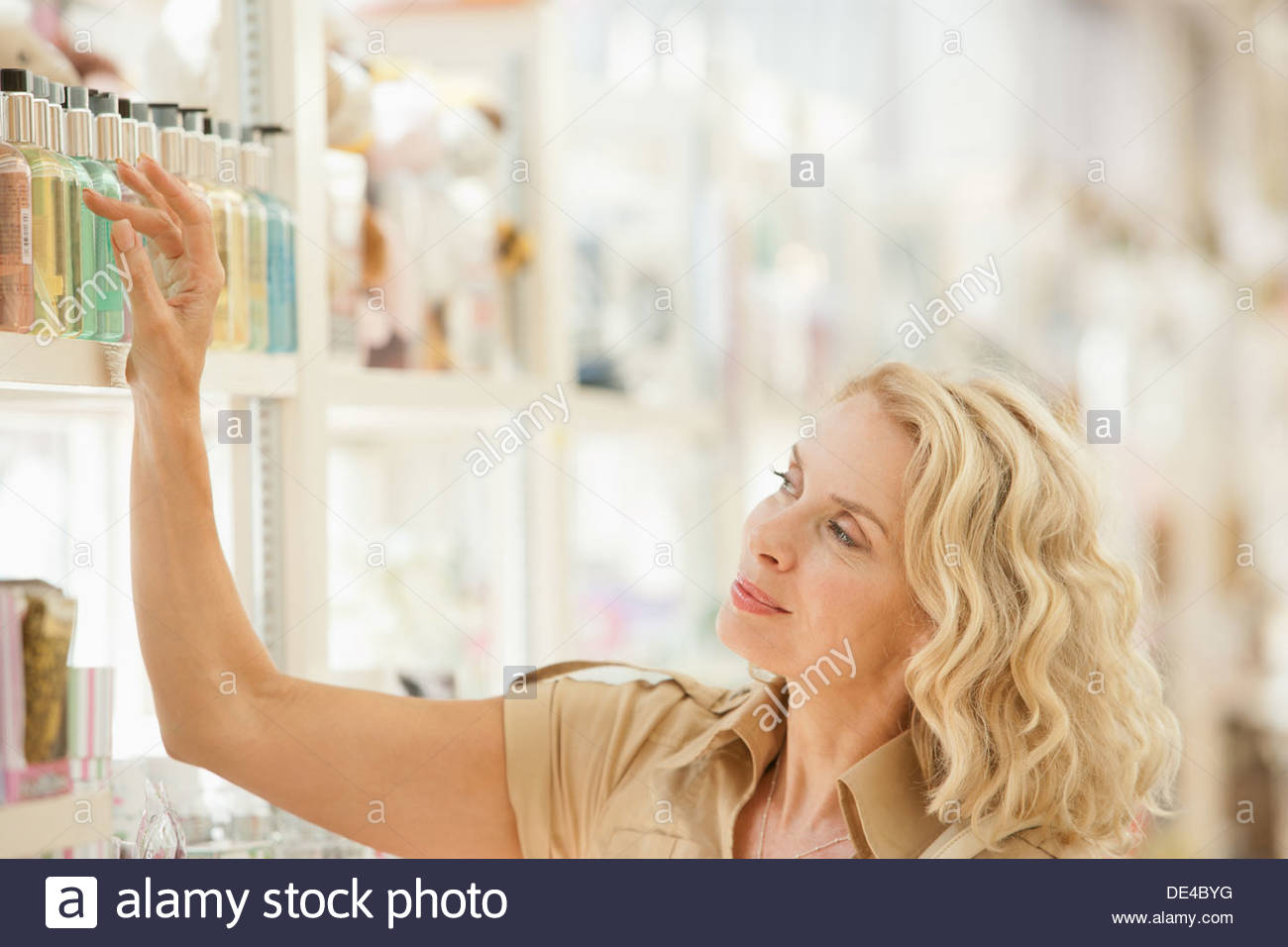 Smiling woman reaching for perfume on store shelf - Stock Image