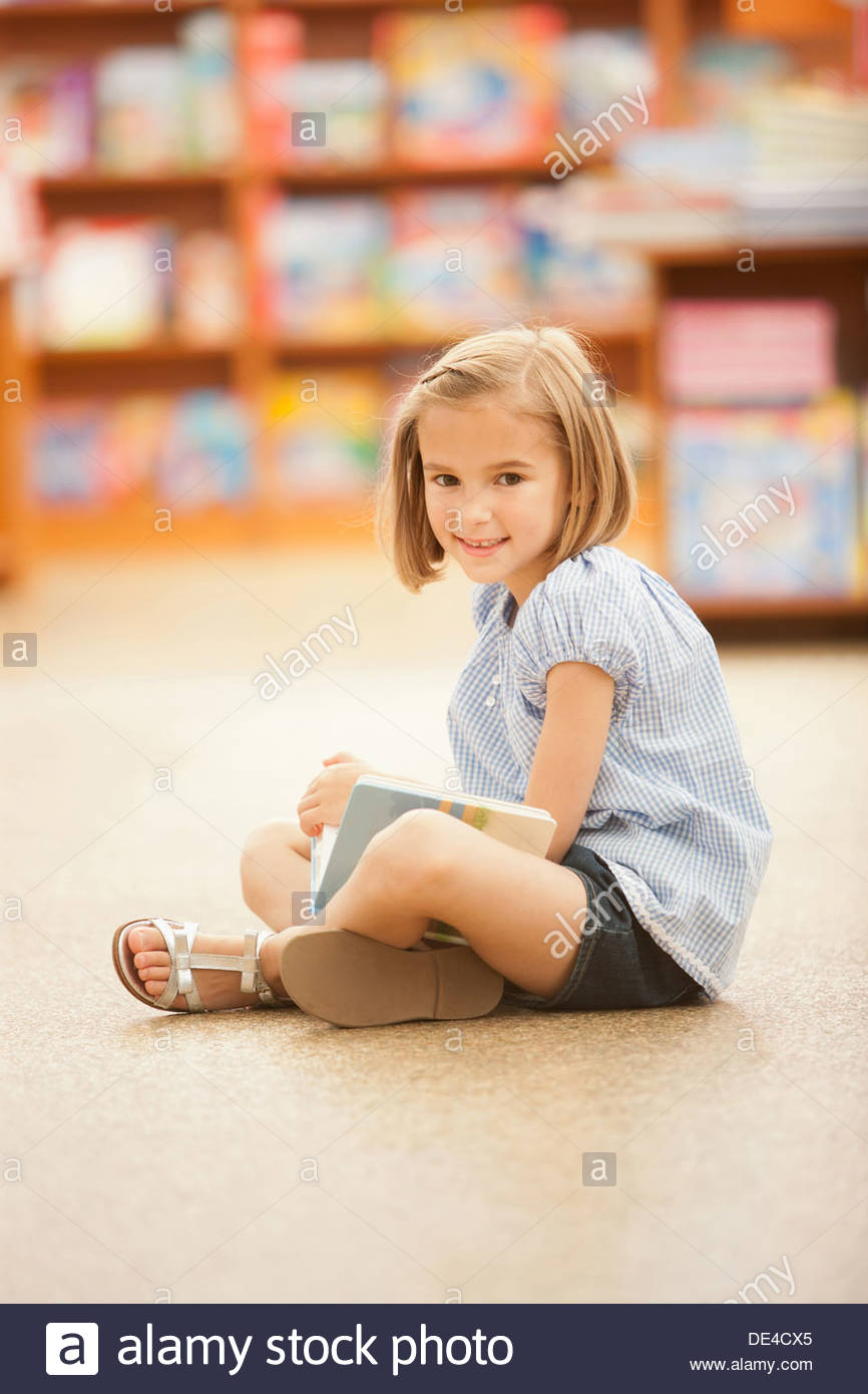Girl sitting on floor of library with book - Stock Image