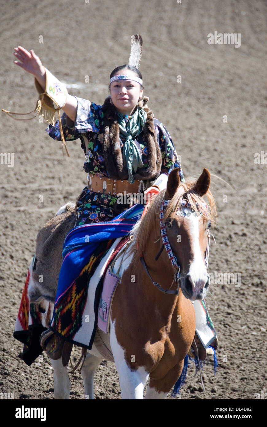 Indian Tribeswoman in traditional dress riding horseback saluting, Ellensburg Rodeo opening ceremony, 2012 WA USA - Stock Image